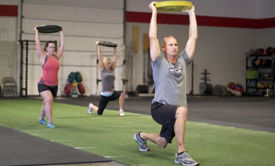 CrossFit Walking lunges with weight plate overhead